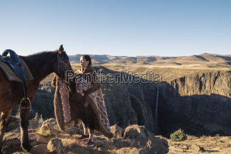 woman stroking horse while standing on