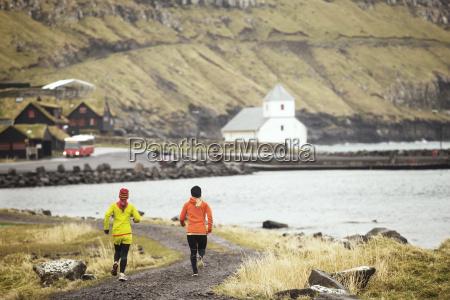 friends jogging at along rocky coastline