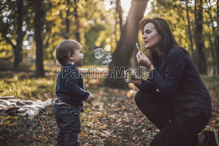 mother and son playing with bubbles