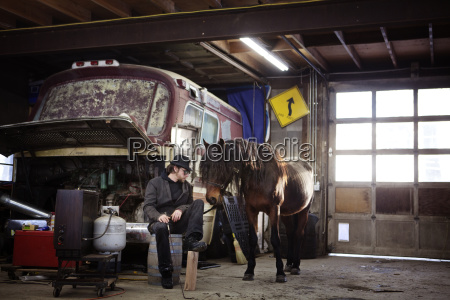 man sitting with horse at workshop