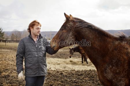 man stroking horse against sky