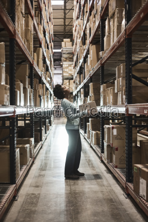 african american female warehouse worker checking