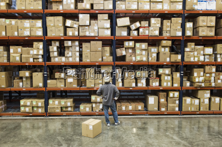 warehouse worker checking inventory next to