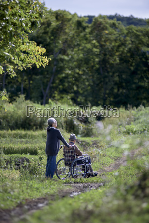 husband and wife elderly woman pushing