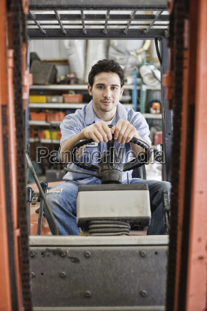 caucasian man employee driving a forklift