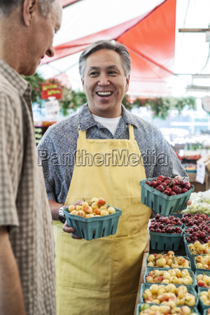 man wearing apron standing at stall