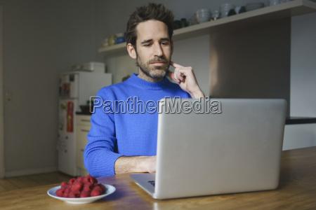 mid adult man sitting with raspberries