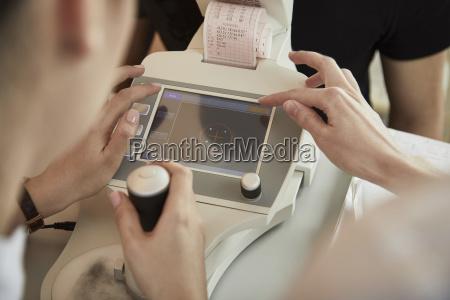 nurses using machinery while examining male