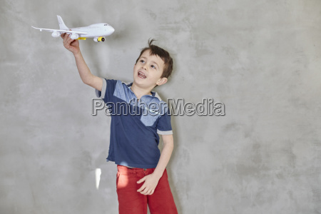 boy playing with model airplane while