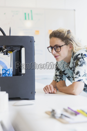 female designer watching 3d printer in
