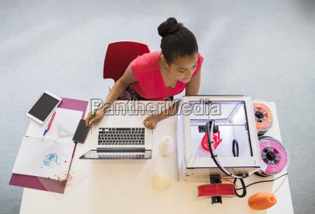 female designer at laptop watching 3d