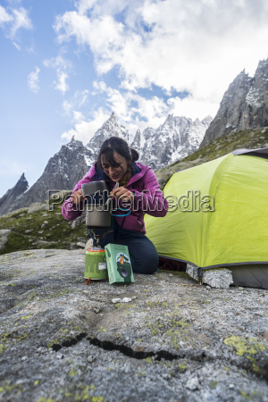 woman cooking soup outside tent in