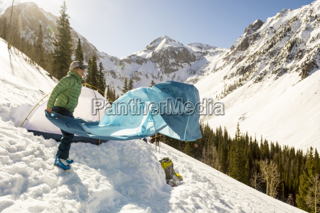 woman packing up tent after camping
