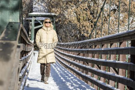 adult woman walking alone across bridge