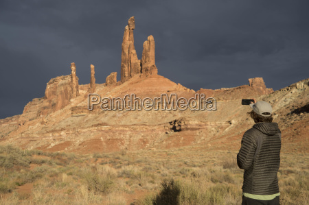 person photographing moses rock tower moab