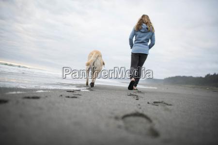 woman with dog walking along beach