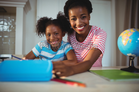 portrait of mother assisting daughter with