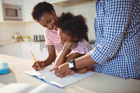 parents assisting daughter with homework
