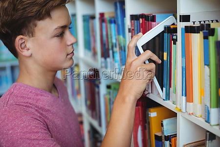 student der digitale tablette im buecherregal
