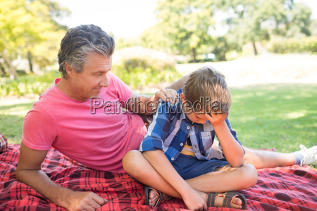 father consoling his son at picnic