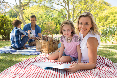 mother and daughter reading book while
