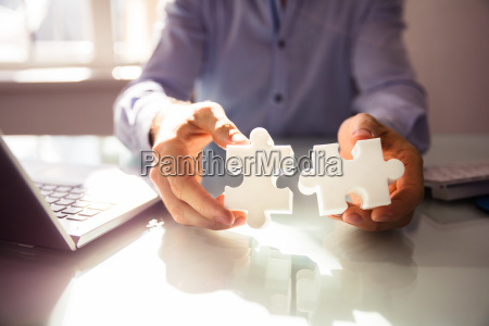businesspersons hand holding two jigsaw puzzle