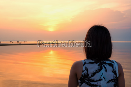 frau beobachtet sonnenuntergang am strand