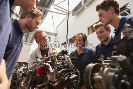 mechaniker der den lehrlingen maschinen niedriger