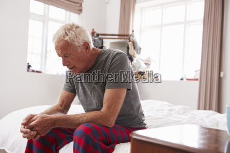 senior man sitting on bed at