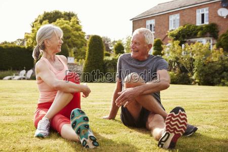 healthy senior couple exercising in garden