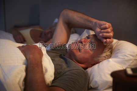 worried senior man in bed at