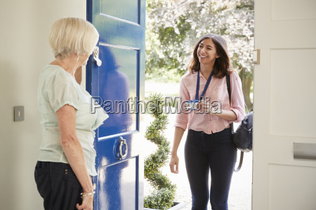 senior woman opens door to female
