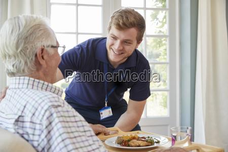 maennliches pflegearbeitskraftumhuellungsabendessen zu einem aelteren mann