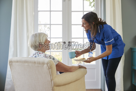 nurse serving tea and biscuits to