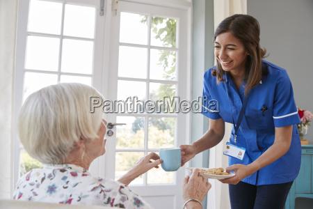 nurse serving tea to senior woman