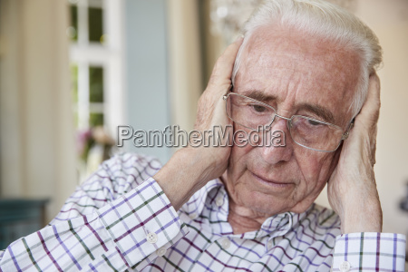 worried senior man at home holding
