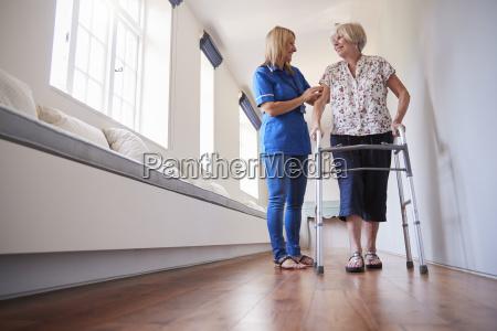 nurse helping senior woman use a
