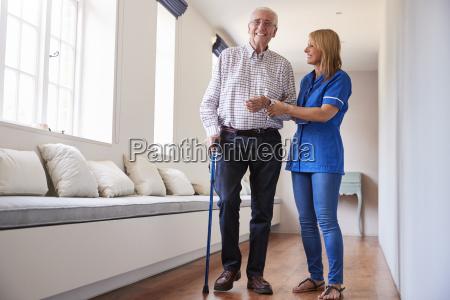 nurse helping senior man walk using