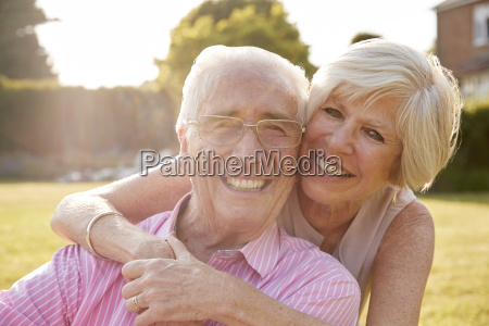 senior couple in garden smiling at