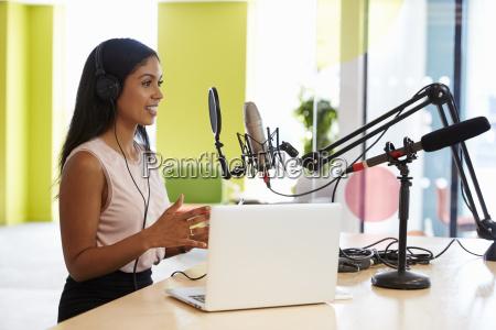 junge mixed rennfrau die einen podcast