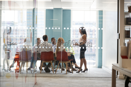 female boss stands addressing colleagues at
