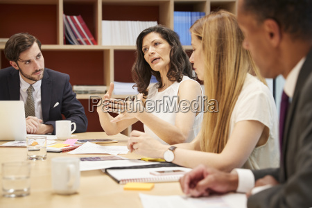 four people at a business boardroom
