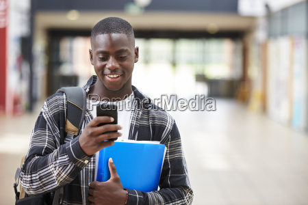 male college student reading text message