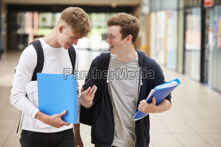 two male college students reading text