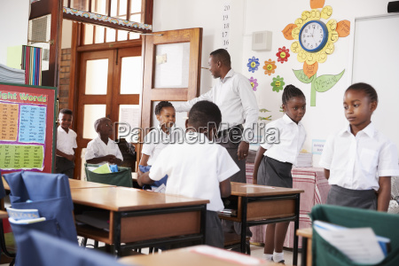 teacher greets kids arriving at elementary