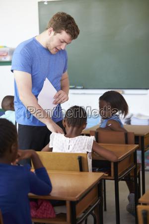 white male teacher helping schoolgirls at