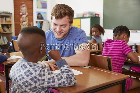 white male teacher helping elementary school