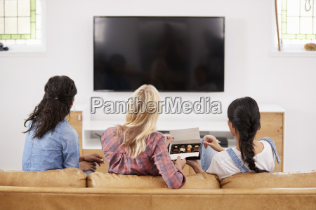 female friends sitting on sofa watching