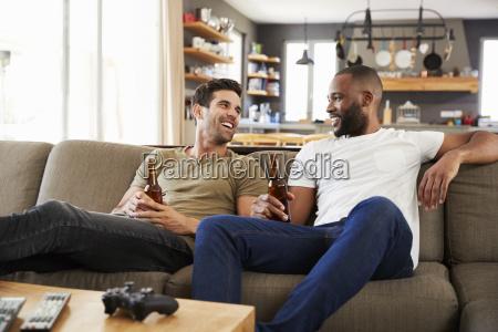 zwei maennliche freunde sit on sofa