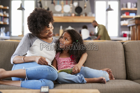 mother and daughter sit on sofa